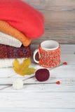 Maglioni tricottati della lana Il mucchio dell'inverno tricottato, autunno copre su fondo rosso e di legno, maglioni, lavori o in Fotografie Stock