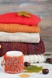 Maglioni tricottati della lana Il mucchio dell'inverno tricottato, autunno copre su fondo rosso e di legno, maglioni, lavori o in Fotografia Stock