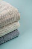 Maglioni tricottati della lana Il mucchio dell'inverno tricottato copre su fondo di legno, maglioni, lavori o indumenti a maglia, Immagine Stock Libera da Diritti