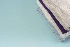 Maglioni tricottati della lana Il mucchio dell'inverno tricottato copre su fondo di legno, maglioni, lavori o indumenti a maglia, Fotografie Stock Libere da Diritti