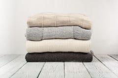Maglioni tricottati della lana Il mucchio dell'inverno tricottato copre su fondo di legno, maglioni, lavori o indumenti a maglia, Immagini Stock Libere da Diritti