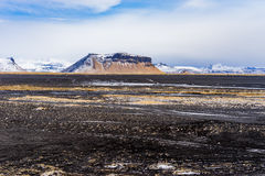 Magma rock plain with mountains in the background. Black magma rock plains in southern Iceland, with snow covered mountain range in the background Royalty Free Stock Photos