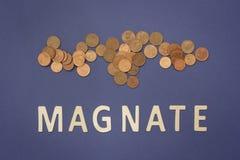 Magnat écrit avec les lettres en bois sur un fond bleu image stock