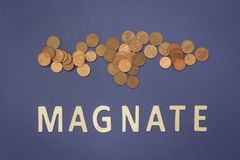 Magnate written with wooden letters on a blue background. To mean a business concept Stock Image
