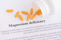Magnesium deficiency diagnosis on paper with pills spilling out. Of a bottle. Close up royalty free stock photo