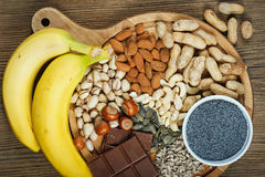 Magnesium in food. Collection natural products containing magnesium as pumpkin seeds, blue poppy seed, cashew nuts, almonds, sunflower seeds, peanuts, hazelnuts Stock Photos