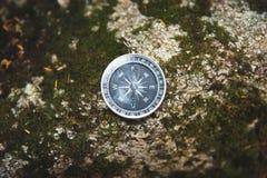 Magnesowy kompas z czarną tarczą na dzikim kamieniu zakrywającym z zielonym mech Pojęcie znajdować sposób i obrazy royalty free