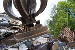 Magnet in Metal Salvage Yard. A powerful electromagnet hovers over a pile of metal scrap Stock Photography