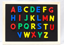 Magnet plastic alphabet on blackboard Royalty Free Stock Photography