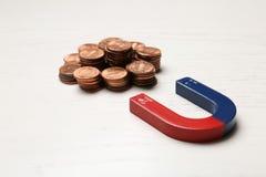 Magnet som tilldrar mynt på träbakgrund arkivbilder