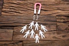 Magnete che attira i candidati di carta sulla Tabella immagine stock