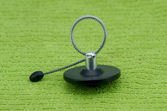 Magnetic bottle security tag on a green fabric Stock Images