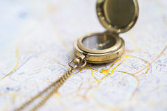 Magnetic compass on a blurry map Royalty Free Stock Photo
