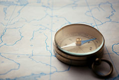 Magnetic compass lying on a map Stock Images