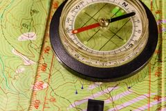 Magnetic compass lying on topographical map Royalty Free Stock Images