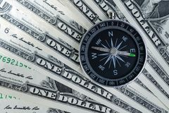 Magnetic compass on pile of dollar bills usning as world economics fortune direction stock images