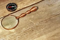 Magnetic Compass and Retro Magnifying Glass on grunge wood board. Background with space for text or image Royalty Free Stock Photos