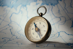 Magnetic compass standing upright on a map Royalty Free Stock Photo