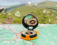 Magnetic compass on tourist map on background of mountain range. Magnetic compass with mirror of sighting mechanisms on a tourist topographical map against the Royalty Free Stock Images