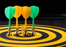 Magnetic dart arrows on yellow dart board. black background Stock Images