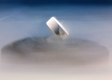 Magnetic levitation. A small rare earth magent levitating above a superconductor. Bathed in liquid nitrogen Stock Photography