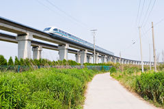 Magnetic levitation train. Travels at 431 km or 270 miles per hour through the green field of suburban shanghai stock photo