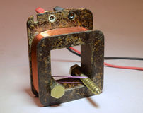 Magnetic Repulsion. Two screws held together with a rubber band inside a coil. Because current flows in the coil they get same magnetic polarity, and are Royalty Free Stock Photo