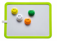 Magnetic smileys. Colorful magnetic smileys on a whiteboard Stock Photos