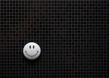 Magnetic smileys. A white smiley on a grid background Royalty Free Stock Image
