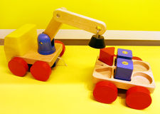 Magnetic toy trucks. An image of some simple and fun colorful wooden toys for young children. A set of magnetic toy crane truck and containers with wheels Stock Photography