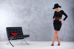 Magnetic vamp woman in a stylish surround. Seductive woman in a black dress and an elegant hat, standing next to a posh leather lounge chair Stock Photos