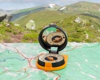 Magnetisch kompas op toeristenkaart op achtergrond van bergketen Royalty-vrije Stock Afbeeldingen
