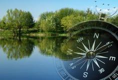 Magnetisk kompass över en stillsam sjö Fotografering för Bildbyråer