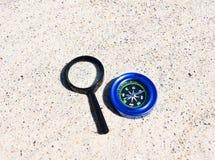 Magnetisk kompass och f?rstoringsapparat i sanden royaltyfri foto