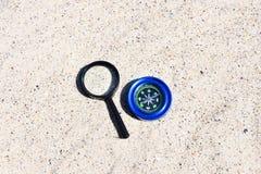 Magnetisk kompass och f?rstoringsapparat i sanden royaltyfri fotografi