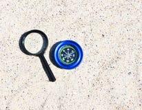Magnetkompass und Vergr??erungsglas im Sand stockfotos