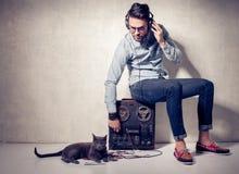 英俊的听到在magnetophone的音乐的人和猫 库存图片