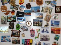 Magnets from travels on the refrigerator experience. Gifts and surprises from their journeys tourists bring magnets on the fridge to leave impressions of the Stock Photos