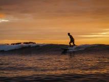 冲浪者在Magnific岩石,日落的尼加拉瓜的骑马通知 库存照片