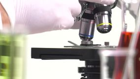 Magnification change lens to a microscope. Ambiance of  laboratory with  microscope on white background stock footage
