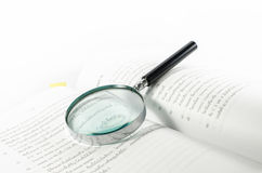 Magnification glass over a opened book Stock Image