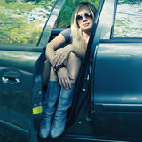 Magnificent blonde driver girl with sunglasses sitting in the bl. Eyewear concept. magnificent blonde driver girl with sunglasses sitting in the blue colored car stock photography
