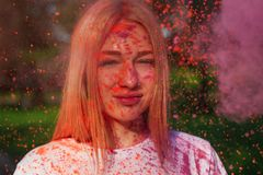 Magnificent blonde woman having fun with colorful pink paint at the park. Concept for festival Holi. Magnificent blonde girl having fun with colorful pink paint royalty free stock photography