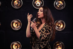 Magnificent brunette in a chiffon leopard dress singing in a silver studio microphone. Mid side shot of magnificent brunette in a chiffon leopard dress singing stock image
