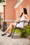 Magnificent brunette sits on bench Royalty Free Stock Photography