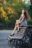Magnificent brunette sits on bench Stock Image