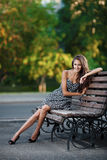 Magnificent brunette sits on bench Royalty Free Stock Images