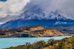 The magnificent cliffs of Los Cuernos. In the clouds are covered with snow. Torres del Paine National Park. Summer in the south of Chile. The concept of extreme royalty free stock photo