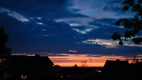Magnificent colorful sky covered with clouds in different shades of blue during sunset in summer, sky is warm and orange, houses i stock video