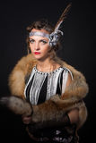 The magnificent girl with a skin of fox and feather in hairstyle in Chicago style. The magnificent girl with a skin of a fox on shoulders and a feather in a royalty free stock image